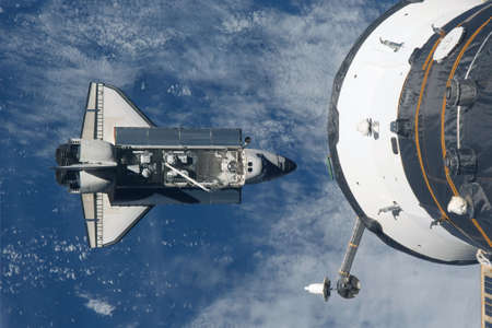 Space shuttle flies under the space station. Elements of this image were furnished by NASA For any purpose