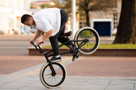 Facet na rowerze BMX wykonuje sztuczkę na przednim kole. W dowolnym celu.