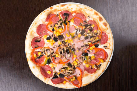 Pizza con pepperoni y champiñones, jamón y pimiento. Para cualquier propósito. Foto de archivo