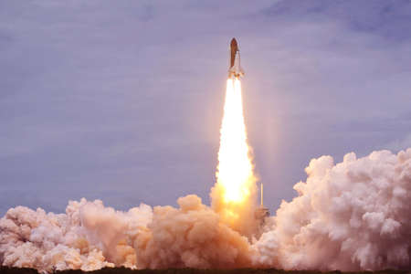 Start des Space Shuttle. Mit Feuer und Rauch. Vor dem Hintergrund des blauen Himmels. Elemente dieses Bildes wurden von der NASA bereitgestellt. Für jeden Zweck. Standard-Bild