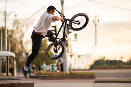 The guy, performing a trick, jumps up from the BMX, from the parapet. For any purpose. Stock Photo