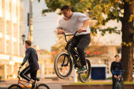 The guy performs a stunt on BMX, jumping from the parapet.