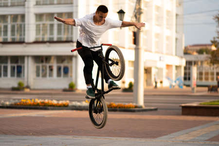 The guy on the BMX bike, releases his hands in a jump. Фото со стока