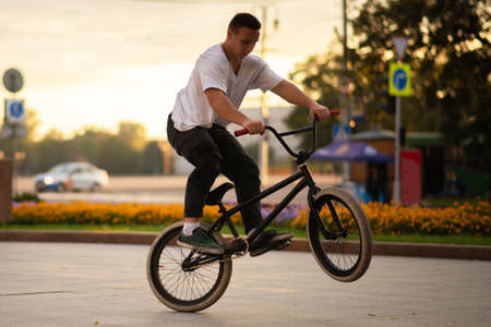 The guy performs a BMX stunt while standing on the rear wheel.