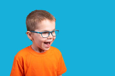 Little boy in glasses is very surprised. Isolated on a blue background.