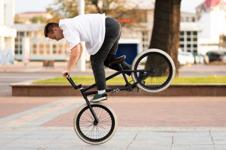 The guy on the BMX bike performs a trick on the front wheel. For any purpose.