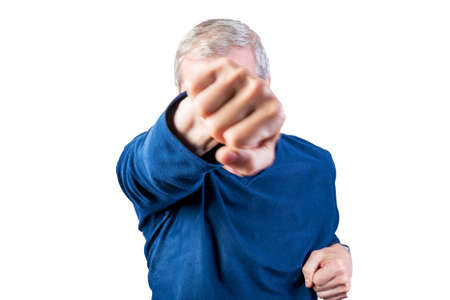 An elderly man demonstrates fist fight. Isolated on a white background. For any purpose.