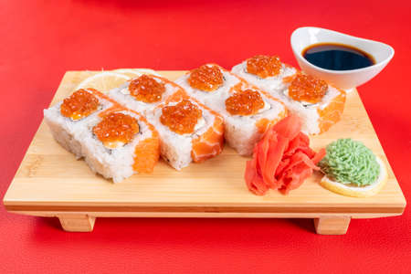 Sushi, with curd cheese, salmon and caviar. On the plank. On a red background. For any purpose.