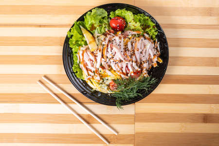 Japanese chicken salad on a black plate. For any purpose. Standard-Bild - 134929963