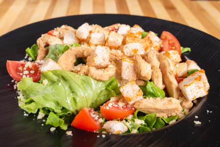 Caesar salad on a black plate, on a wooden background. For any purpose. Standard-Bild - 134930211