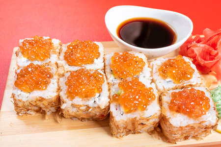 Roll with red caviar, covered with dried tuna chips. Close-up. For any purpose.