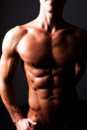 A man demonstrates a beautiful athletic torso. In contrasting light. With shine and water. For any purpose.