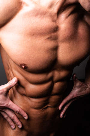 Beautiful, athletic, male torso. In contrast lighting. With shine and water. For any purpose.
