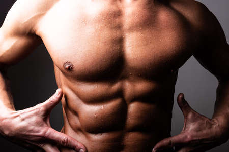 Beautiful, athletic, male torso. In contrast lighting. A man holds his hands near the press. For any purpose.