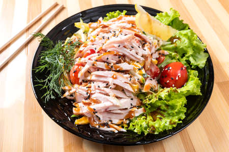 Japanese chicken salad on a black plate. For any purpose. Standard-Bild - 134921441