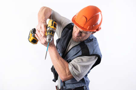 Builder with a funny expression, in a helmet, with a cordless drill. For any purpose.