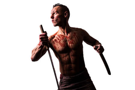 An athletic man, in blood, with a Japanese sword, strikes. Isolated on a white background. 写真素材