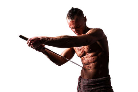 A man with a katana, in blood, makes hara-kiri. Isolated on a white background.