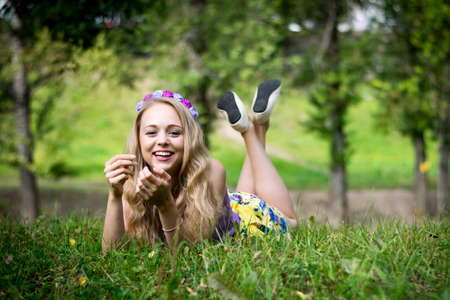 Beautiful blonde girl is lying in the grass and laughing.