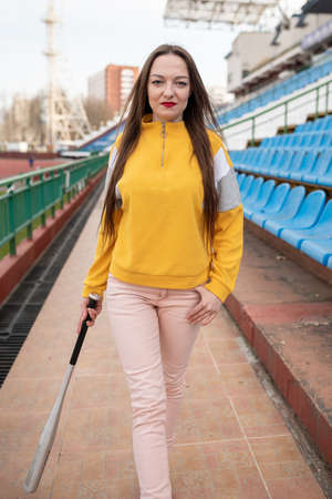 Girl with a bat in an empty stadium. Фото со стока - 146874010