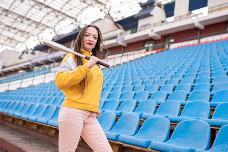 Girl with a bat in an empty stadium.