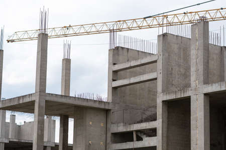 Reinforced concrete construction site and crane in cloudy weather.