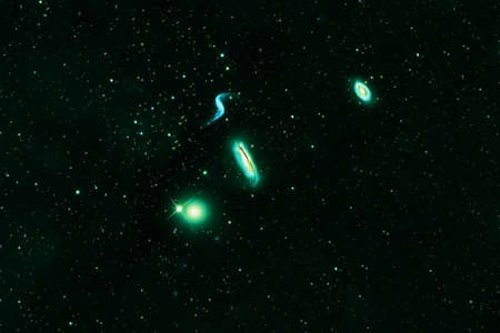 Green galaxies on a black background.