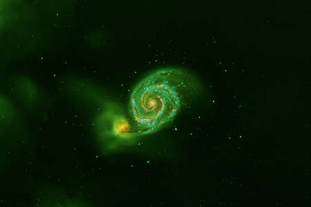 Green spiral galaxy on a dark background.