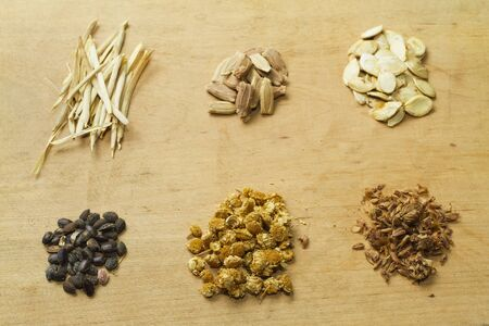 wallflower: Pine-tree, chamomile, lavender, pumpkins and wallflower seeds on wooden background  Stock Photo