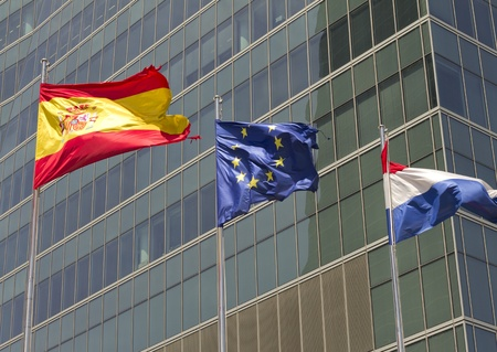 European, spanish and french flag with modern building on the background