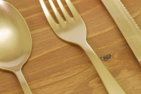 serving utensil: Golden spoon, fork and knife on wooden table Stock Photo