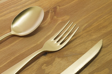 Golden spoon, fork and knife on wooden table photo