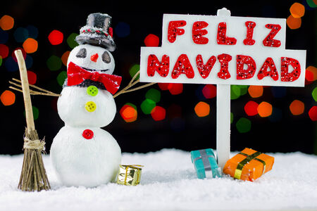 Snowman with a Merry Christmas signpost written on spanish, bokeh lights photo
