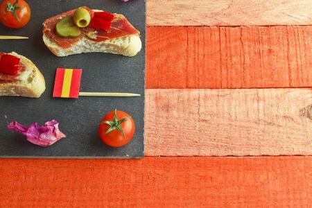 gherkin: Spanish tapa with ham, bread, pepper, olive, gherkin and a spanish flag brochette Stock Photo