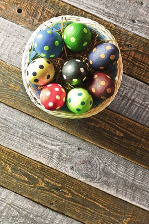 Easter eggs on a basket on wooden background photo