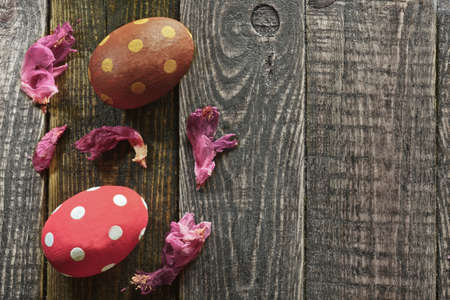 Two Easter eggs and flowers on wooden background photo
