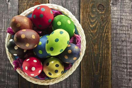 Easter eggs and flowers on a basket on wooden background photo