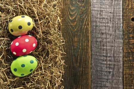 Three Easter eggs and hay on wooden background photo