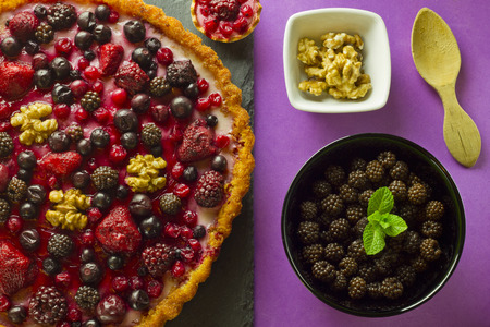 Autumn fruits cake and ingredients on purple background photo