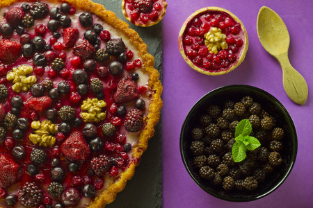 Autumn fruits cakes and ingredients on purple background photo