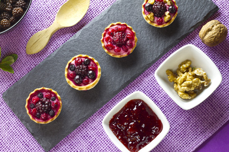Autumn fruits cakes on a slate plate and ingredients on purple background photo