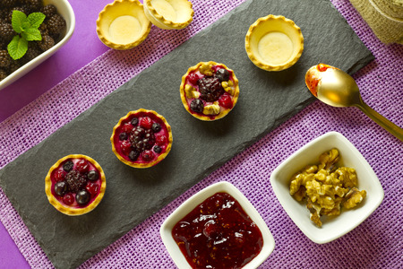 Autumn fruits cakes, pie shells and bowls with ingredients on purple background photo