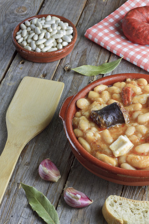 Spanish fabada in a earthenware dish on a wooden table with ingredients Archivio Fotografico