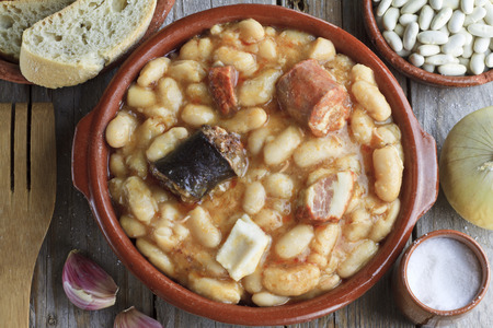 Spanish fabada in an earthenware dish on a wooden table with ingredients