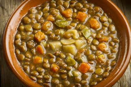 Close up of a vegetable lentil soup on a wooden table, with lentils, carrots, pepper, and potatoes