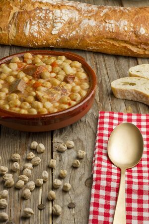 pot belly: Spanish Cocido, rustic bread, golden spoon and white and red napkin on a wooden table