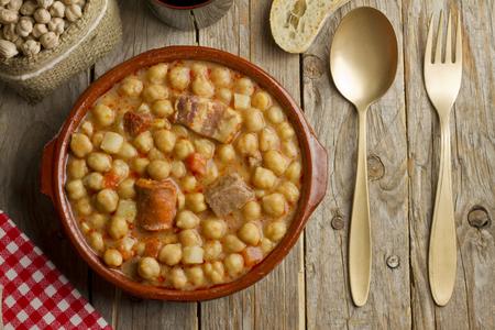 Cocido espagnol dans un pot en terre cuite et une fourchette dorée et une cuillère sur une table en bois