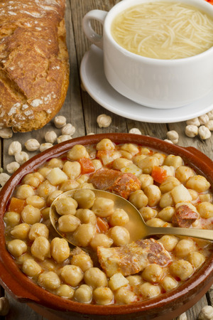 pot belly: Spanish Cocido with spoon, soup in a white bowl and bread on a wooden table Stock Photo
