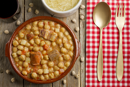 Spanish Cocido in an earthenware pot, golden fork and spoon on a white and red napkin and dried chickpeas