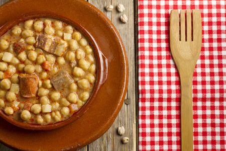 pot belly: Spanish Cocido in an earthenware pot and dish, dried chickpeas and a wooden fork